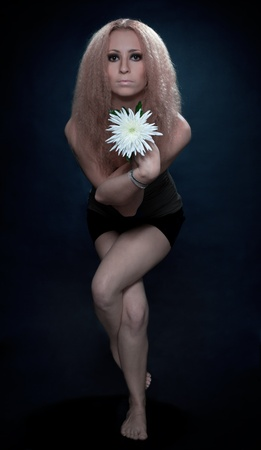 beauty studio shoot of woman standing in yoga pose with white flower photo