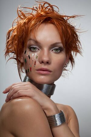 tudio fashion portrait cyber woman with red hair, chip in her face looking in camera photo