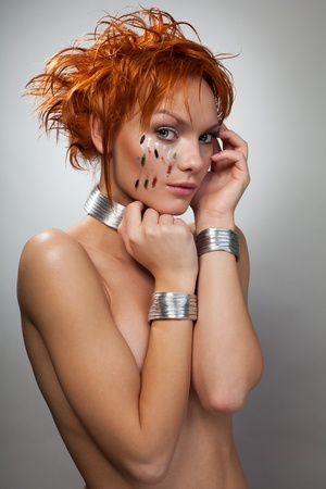 Afraid beautiful woman from future with red hair, chips and metal bracelets looking at camera Stock Photo - 8433962