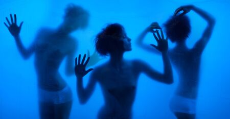 Moving and dancing silhouettes of women behind the washing curtains and blue background photo