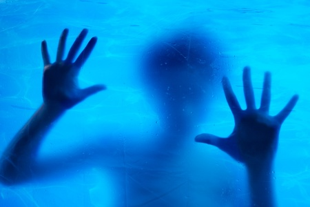 Woman swimming underwater behind the glass