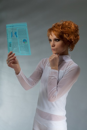 Beautiful woman hold hi-tech newspaper on transparent screen (professional makeup and hair stylist) photo