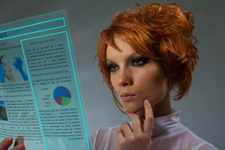 futuristic woman: Future newspaper  - beautiful woman holding transparent futuristic monitor (shoot with professional makeup and hair stylist) Stock Photo