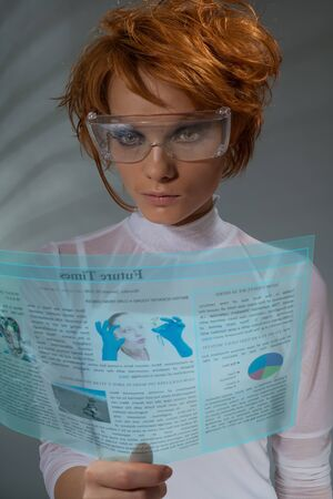 Future newspaper on transparent screen  - beautiful woman holding transparent futuristic monitor (shoot with professional makeup and hair stylist) photo
