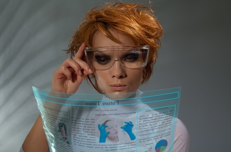 Futuristic beautiful woman reading Newspaper on transparent flexible screen(professional makeup and hair stylist) photo