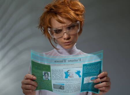 Beautiful woman reading newspaper from flexible hi-tech display (professional makeup and hair stylist)