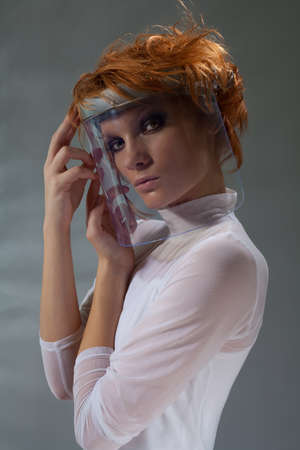 Futuristic woman in glass mask looking at camera in white clothes photo