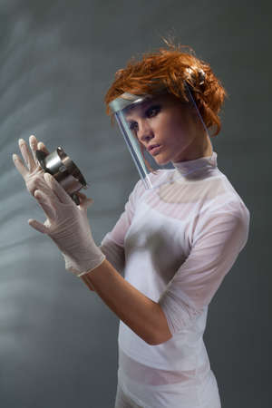 Scientist woman examine metal part of machinery  made with professional makeup and hair stylist photo