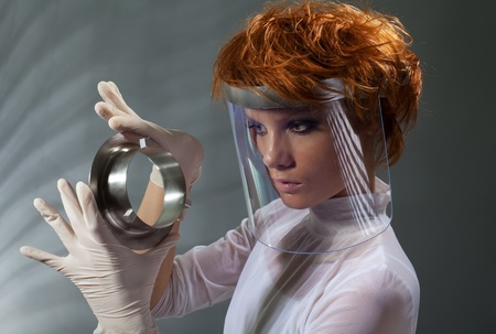 Futuristic woman examine metal detail holding it in latex gloves and wearing white clothes made with professional makeup and hair stylist photo