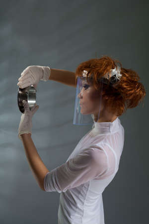 laboratory woman examining detail processing quality control with professional makeup and hair stylist photo