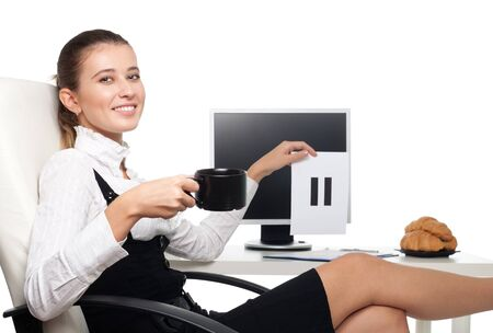 Young business woman sitting on chair at the desk in office drink coffee and hold pause sigh photo