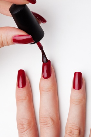 Painting female fingernails with red enamel close-up on white background Archivio Fotografico