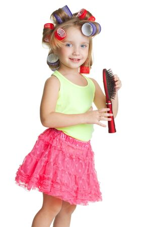 Little girl play big and barber with comb and hair rollers photo