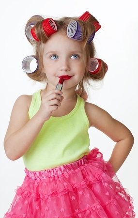 pink posing: Little girl play big applying lipstick and wearing hair rollers