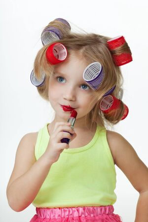rollers: Little girl pretend to be old applying lipstick and wearing hair rollers