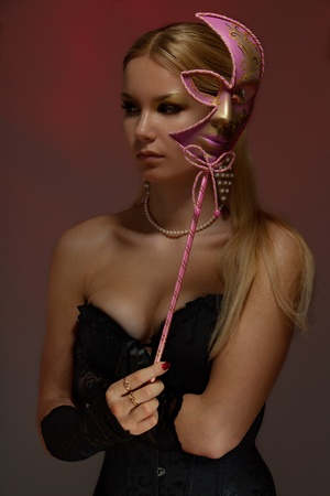Calm gorgeous young woman at masquerade holding pink venetian mask photo