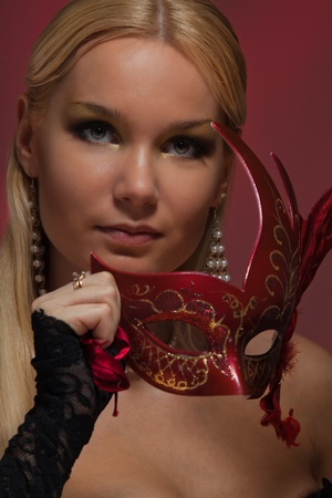 Woman with venetian mask and wearing black corset photo