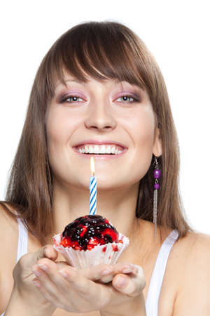 Young woman with a cake with candle at her birthday smiling photo