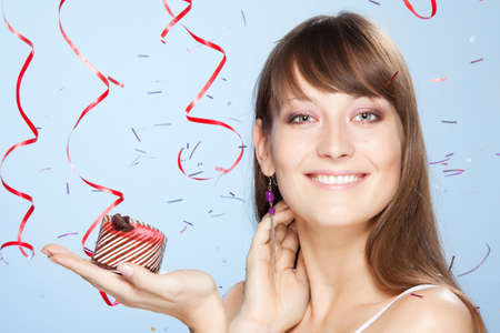 Smiling young girl holds cake with confetti and ribbons on background Stock Photo - 9100983
