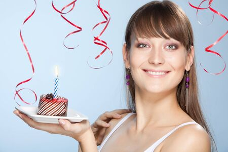 Young woman with a cake with candle at her birthday smiling with flying ribbons on background standing in profile photo