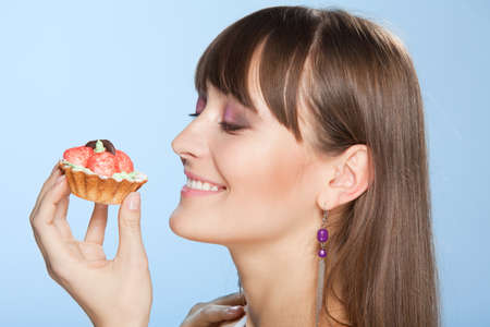 Happy woman with tart cake smiling and admire to eat it photo