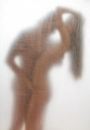 Sexy couple together in the shower standing behind the transparent bath curtain