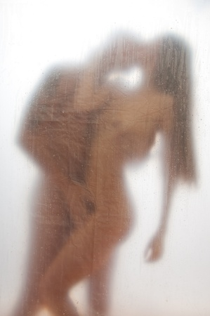 Sexy couple kissing in the shower standing behind the transparent bath curtain