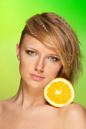 health and beauty: Beauty portrait of a young beautiful woman with orange fruit