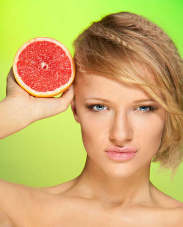 Beauty portrait of confident young attractive woman with grapefruit photo
