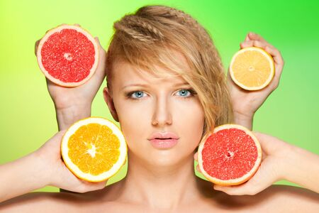 Close up portrait of woman with many juicy citrus fruit in four hands photo