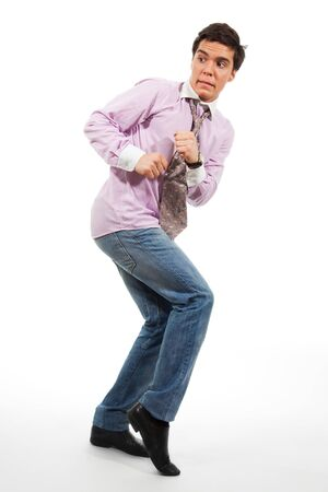 scared man: A man walking by stealth with grimace on his face, wearing jeans, shirt and tie, isolated on white