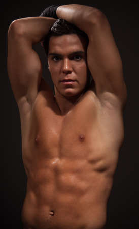 Handsome muscular man with strong arms on dark background photo