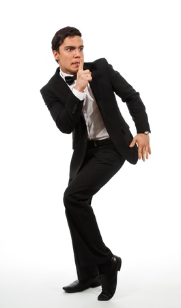 Business man in formal clothes showing a shh gesture calling for silence