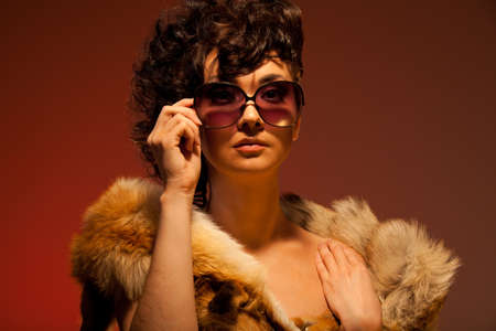 respectable: Respectable glamorous woman wearing fur and glasses Stock Photo