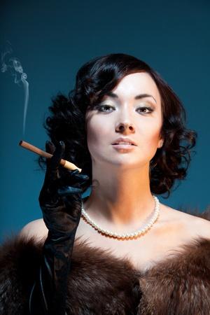 Enjoying cigar - woman standing and smoking cigar on blue background photo