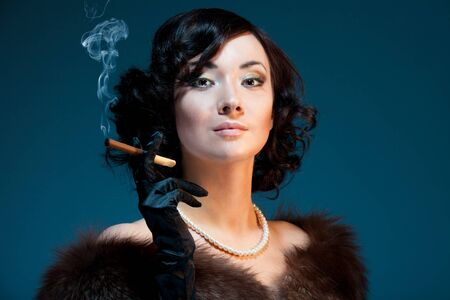 Woman smoking cigar with retro style look photo