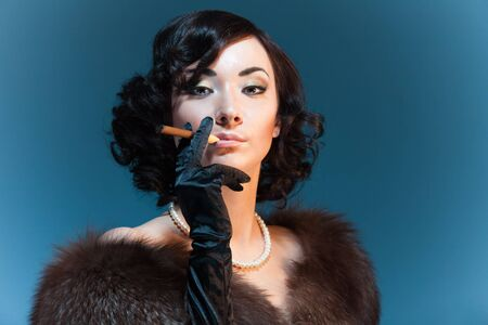 rich flavor: Retro style woman smoking cigar and wearing fur, movies star look Stock Photo