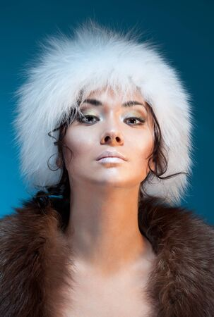 Portrait of a Mongolian Asian beautiful woman in a winter white fur hat photo