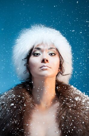 Beauty shoot of majestic Mongolian woman with falling snow and warm light from fire wearing fur hat and coat photo