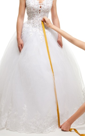 Measuring the size of brides skirt with centimeter, isolated on white photo