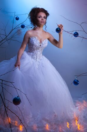 Bride in a wedding dress walking between winter trees decorated with Christmas balls, shoot with both continuous and instant flash light made with professional makeup artist and hairdresser photo
