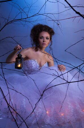 Bride sitting in wedding dress with lamp in fairytale forest at winter, like in a dream, shoot with both continuous and instant flash light made with professional makeup artist and hairdresser photo