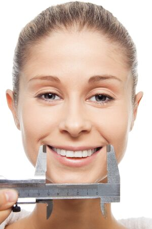Measuring smile size with trammel - close-up portrait, isolated on white photo