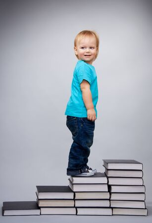 Young boy walking on top of the leader made of books pile photo