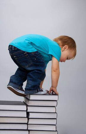 Kid climbing on top of the books pile describing education efforts Stock Photo - 9097110