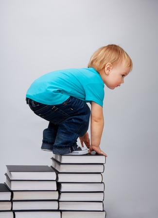 climbed: A young kid has climbed on top of the books steps Stock Photo