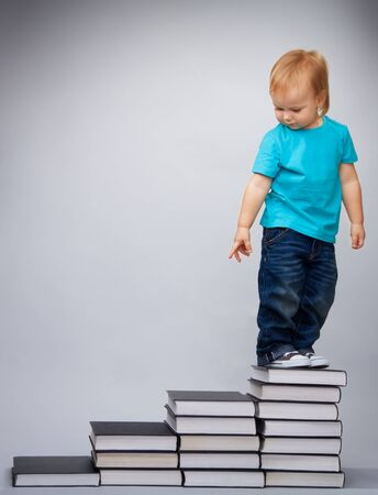 ni�o escalando: Chico de l�der de educaci�n temprana de la pila de libros permanente y mirando hacia atr�s