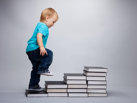 infants: A toddler climbing on a steps made of books Stock Photo