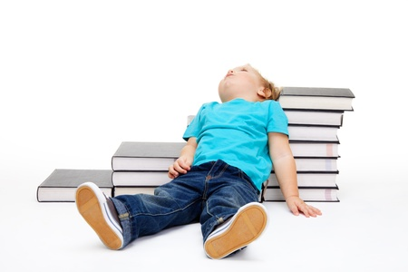 Kid tiered of education lay exhausted on the floor and steps made of books photo