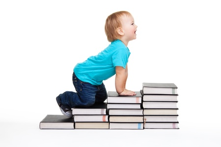 A toddler creeping for knowledge on the steps made of books Stock Photo